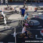 Dzieci w kaskach i na rowerach w miasteczku rowerowym jeżdżą zgodnie ze znakami