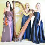 Zdjęcie trzech kobiet w sukniach balowych przy harfie, jedna z nich trzyma skrzypce