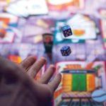 Ręka podrzucająca dwie kostki do gry