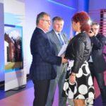 Uroczystość otwarcia szkoły w Murowanej Goślinie po rozbudowie - na scenie starosta, wicestarosta oraz osoby z dyplomami i różami