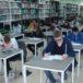 biblioteka z ustawionymi pojedynczymi ławkami i uczniami piszącymi konkurs Złota Żaba