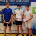 trzech zawodników na tle ścianki promocyjnej Pierwszego Kroku Wioślarskiego na terenie powiatu poznańskiego