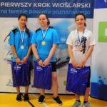 trzy zawodniczki z medalami na tle ścianki Pierwszego Kroku Wioślarskiego na terenie powiatu poznańskiego