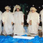 pięć osób występujących na scenie w przebraniu aniołów