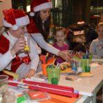 dzieci rysujące przy stole, siedzące z św. Mikołajem