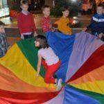 dzieci bawiące się kolorowym materiałem