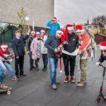 grupa osób w czapkach świętego Mikołaja na hulajnodze, deskorolce, trzymające mapę
