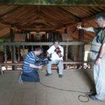 na zdjęciu trzy osoby, dwie osoby to operatorzy mikrofonu i kamery, trzecia osoba gra na skrzypcach