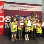 """dzieci w odblaskowych kamizelkach """"bezpieczni w powiecie"""" pozują do zdjęcia na ściance OSiR w Mosinie"""