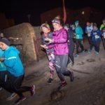 zdjecie wykonane nocą, grupa biegaczy przebiega przez bramę