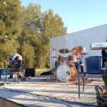 zdjęcie ukazujące scenę z ustawionymi instrumentami, osoby wykonują próbę dźwiękową