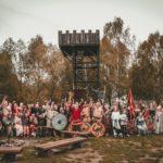 zdjęcie z Wiecu Piastowskiego w Grodzie Pobiedziska, grupa ludzi pozuje do zdjęcia w strojach stylizowanych na czasy wczesnośredniowieczne, wyposażeni w tarcze, miecze i flagi