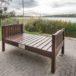 Drewniana ławeczka nad brzegiem jeziora