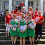 grupowe zdjęcie Pań na schodach z uszytymi poduszkami w kształcie serc