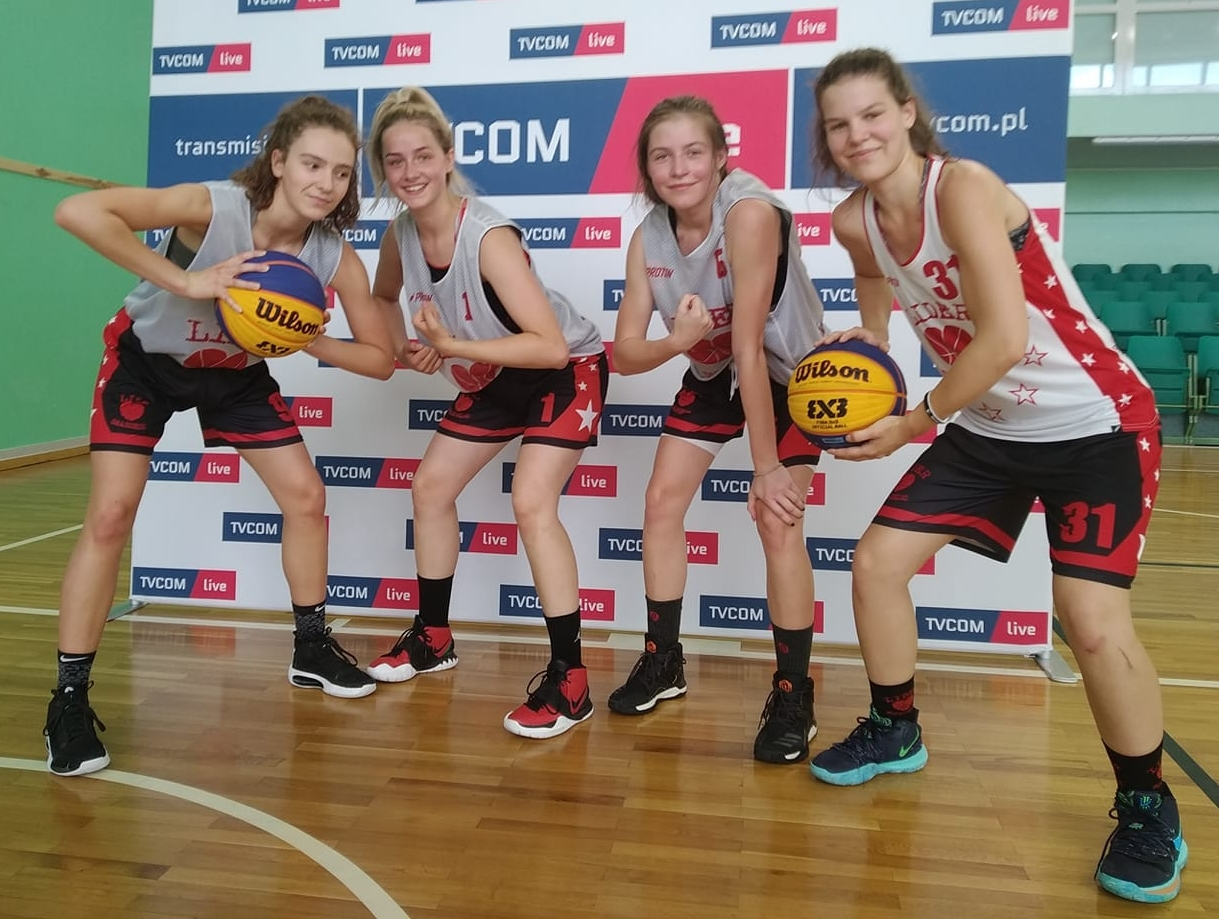koszykarki Llider Swarzędz pozujące z piłkami koszykowymi na hali sportowej