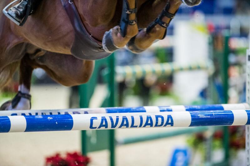 zdjecie konia w skoku nad przeszkoda z napisem cavaliada